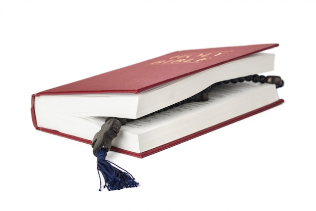 Biblia sobre un fondo blanco. libro sagrado y rosario de madera.