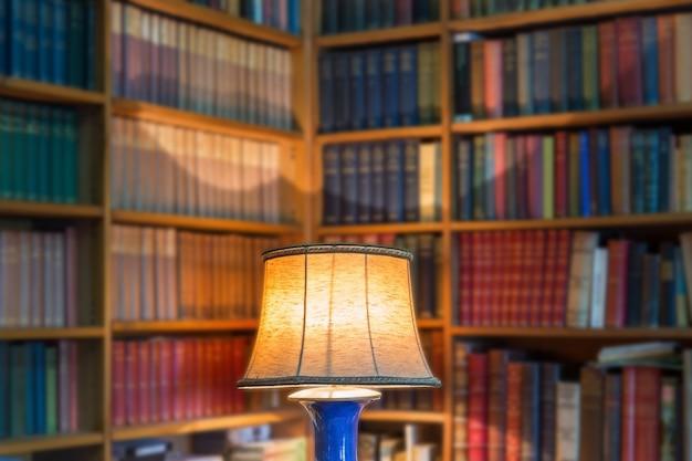 Biblioteca de ángulo de libros antiguos y conocimiento. la pantalla de la lámpara en primer plano.