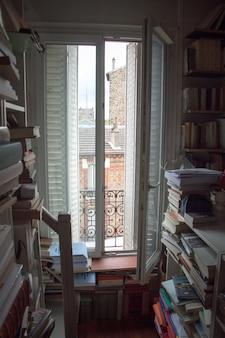 Biblioteca de casa con una gran cantidad de libros y una ventana con persianas en un pequeño apartamento