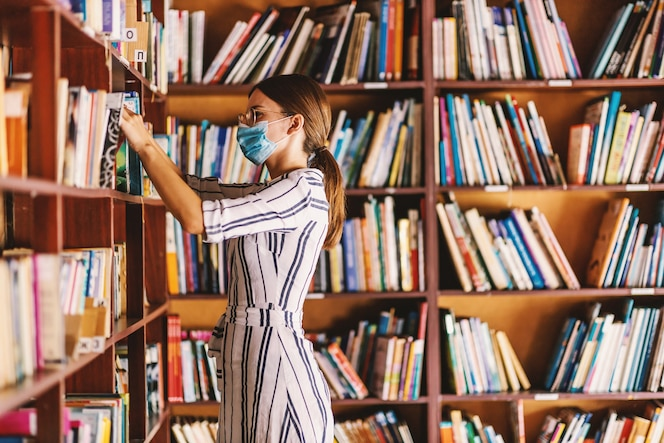 Bibliotecario atractivo joven con mascarilla en la búsqueda de un libro mientras está de pie en la biblioteca durante la pandemia del virus corona.