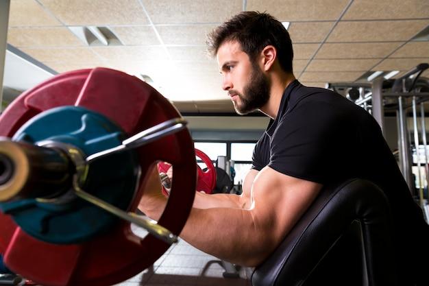 Bíceps predicador banco brazo curl entrenamiento hombre en el gimnasio