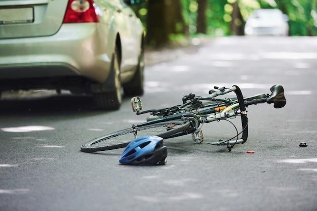 Bicicleta y accidente de coche de color plateado en la carretera en el bosque durante el día