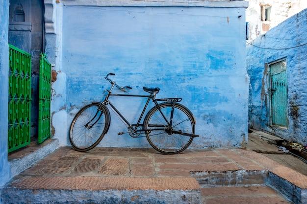 Bicicleta apoyada en la pared azul