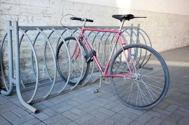 La bicicleta está atada al estante de la calle.