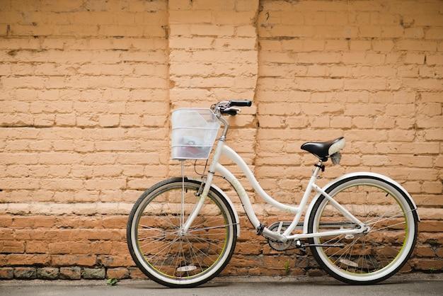 Bicicleta de ciudad blanca con pared de ladrillo