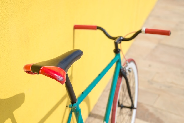 Una bicicleta de ciudad fija en pared amarilla
