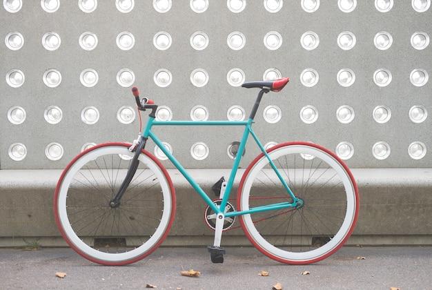 Una bicicleta de ciudad fija en una pared verde y blanca