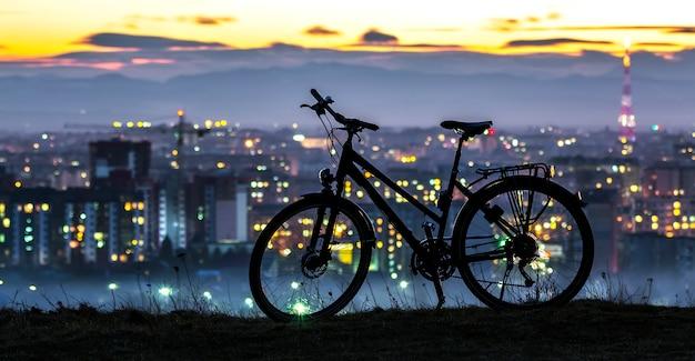 Bicicleta deportiva moderna de la ciudad de pie solo sobre el fondo de la ciudad de noche