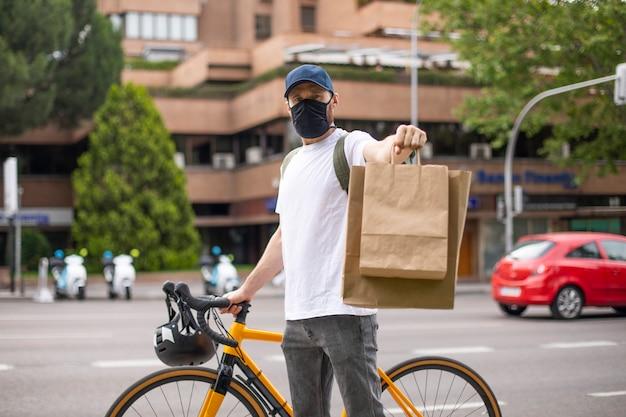 Bicicleta de entrega de alimentos con máscara de coronavirus con mochila y bolsas