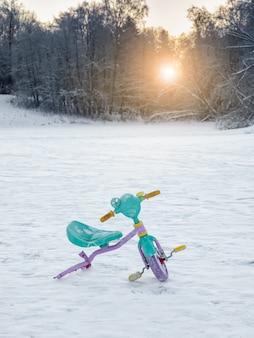 Bicicleta infantil rota abandonada en la nieve. el fin del concepto de vacaciones.