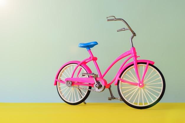 Bicicleta de juguete roja con sillín azul sobre fondo azul y amarillo. bicicleta para paseos por la ciudad y la comarca.