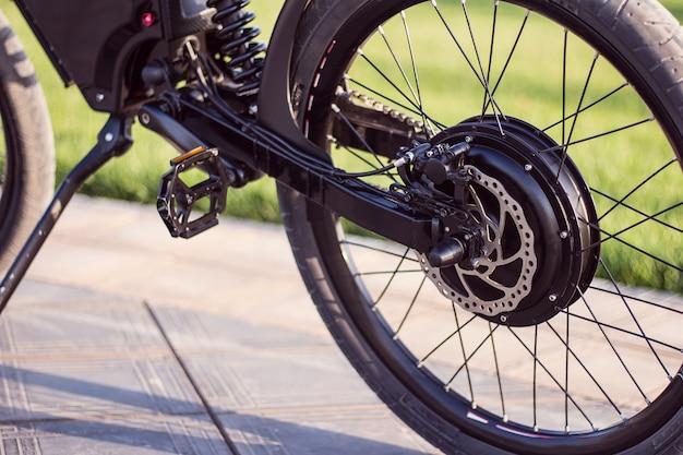 Bicicleta de motor de bicicleta eléctrica de cerca con pedal y amortiguador trasero.