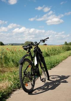 Una bicicleta con motor eléctrico se encuentra en un camino de piedra junto al campo verde de primavera con amapolas rojas