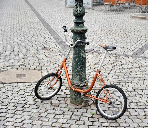 Bicicleta naranja encadenada a un poste