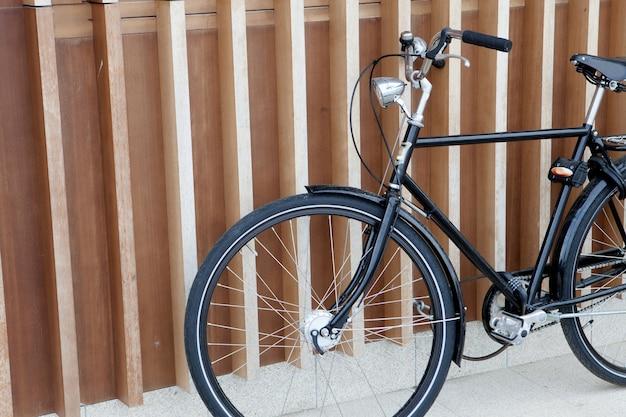 Bicicleta negra apoyada en una pared moderna.