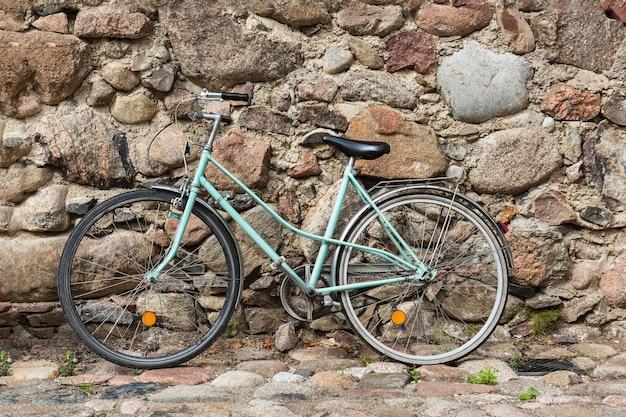 Bicicleta oxidada azul vieja contra la pared vieja en la calle.