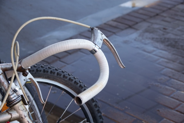 Bicicleta oxidada vieja de la vendimia cerca del muro de cemento