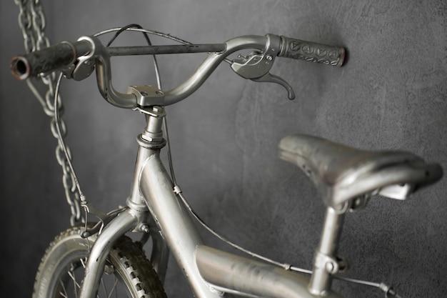 Bicicleta plateada colgando de cadenas contra la pared en el estudio