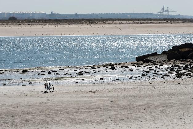 Bicicleta en la playa con paisaje industrial.