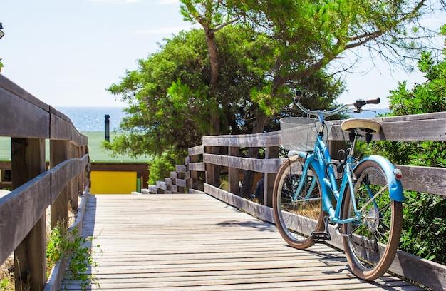 Bicicleta en un puente de madera en el camino a la playa