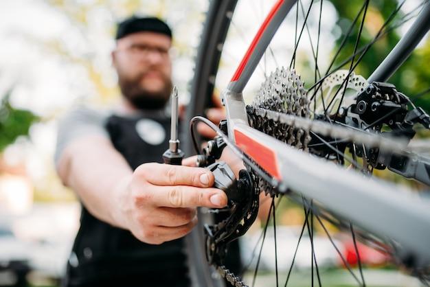 Bicicleta de reparación de mecánico de bicicletas con palanca de cambios rota, taller de ciclo al aire libre. bicicleta deportiva, hombre de servicio trabaja con rueda