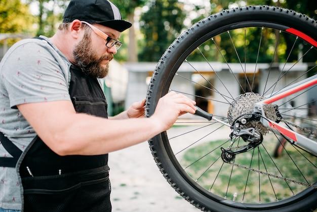 Bicicleta de reparación de mecánico de bicicletas, taller de ciclo al aire libre. el técnico trabaja con la rueda y la palanca de cambios