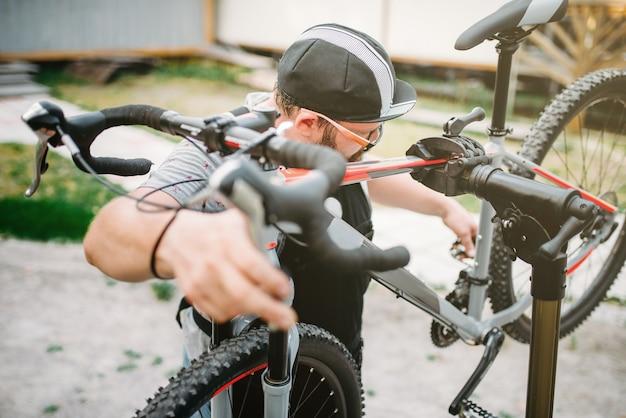 Bicicleta de reparación de mecánico de bicicletas, vista superior. taller de ciclo al aire libre. deporte de ciclismo, hombre de servicio barbudo trabaja con rueda