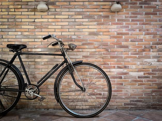 Bicicleta retra delante de la pared de ladrillo vieja.
