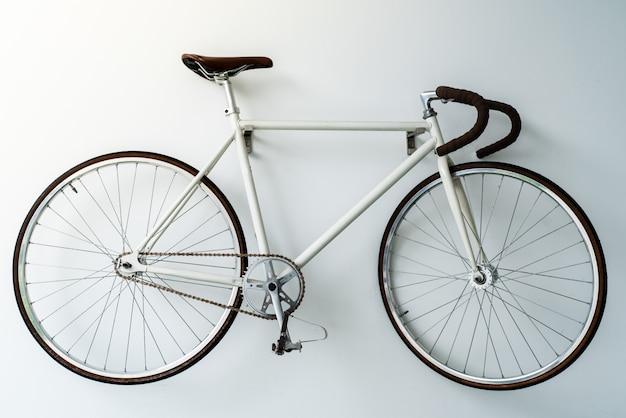 Bicicleta retro colgada en la pared blanca