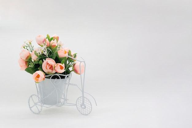 Bicicleta retro con maceta de flores sobre fondo claro.