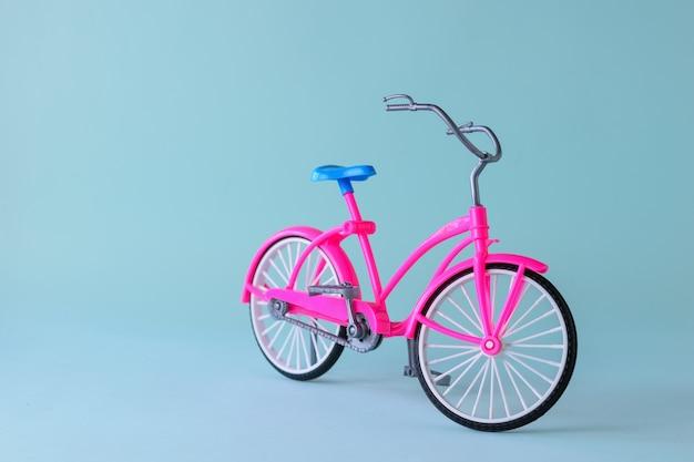 Bicicleta roja con sillín azul sobre fondo azul claro. bicicleta para paseos por la ciudad y la comarca.