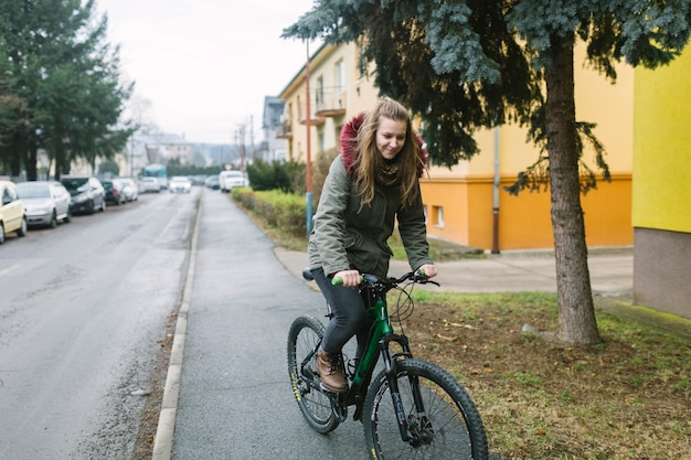 Bicicleta rubia joven del montar a caballo de la mujer en el camino en la ciudad