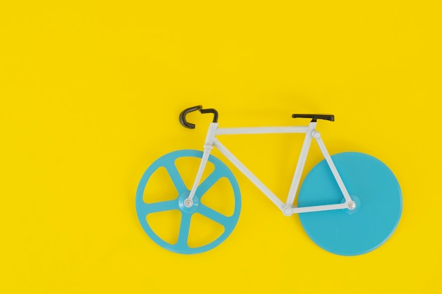 Bicicleta con ruedas azules sobre un amarillo brillante