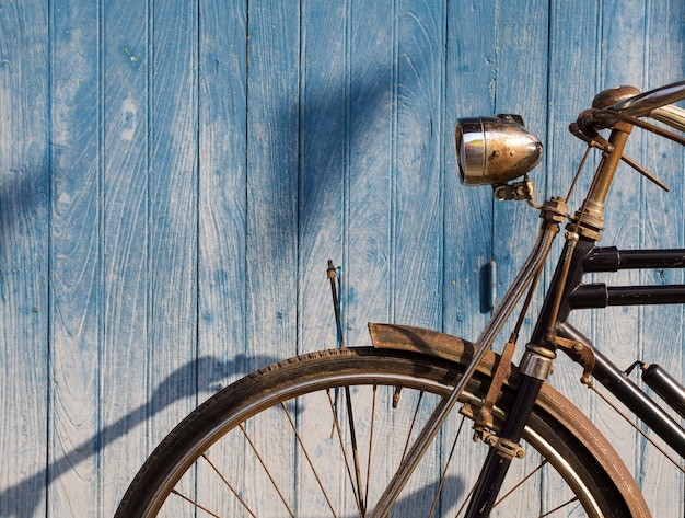 Bicicleta vieja estacionada delante del piso de tablón azul