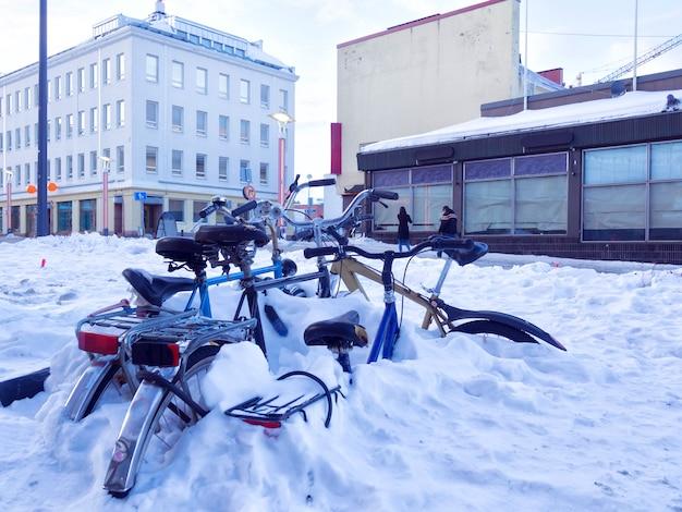 Bicis de la ciudad cubiertas de nieve en una calle