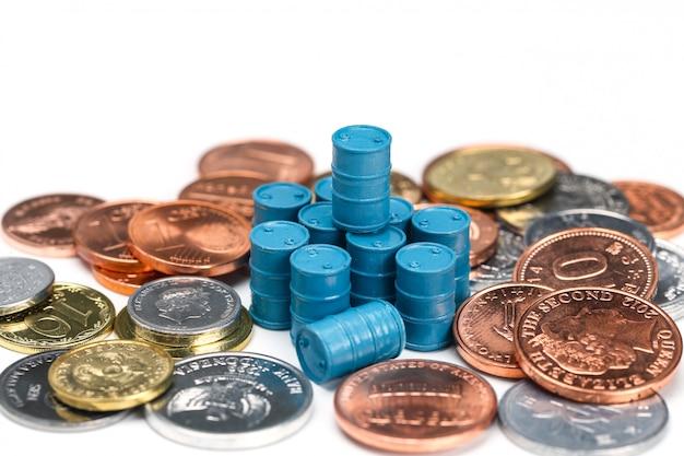 Bidones de aceite azul y monedas sobre fondo blanco.