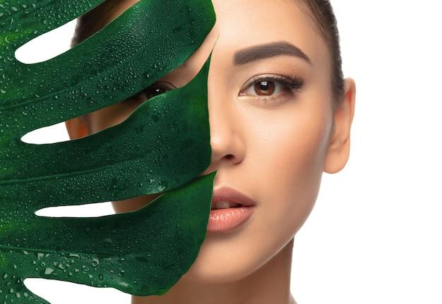 Bien cuidado. retrato de mujer joven hermosa sobre fondo blanco de estudio. concepto de cosmética, maquillaje, tratamiento natural y ecológico, cuidado de la piel. aspecto brillante y saludable, moda, salud. copyspace.