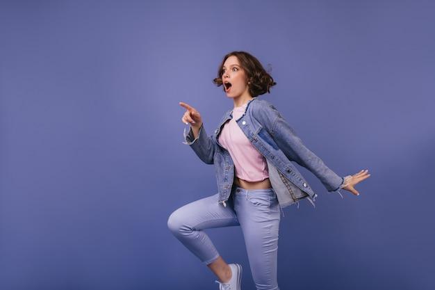 Bien formada chica sorprendida mirando en la distancia. foto interior de glamorosa mujer caucásica en pantalones morados.
