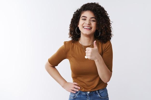 Bien gracias. feliz carismático riendo joven atractiva chica rizado cabello oscuro mostrar pulgar hacia arriba sonriendo satisfecho aprobar increíble gran cosa como elección genial recogiendo traje amigo fecha, fondo blanco