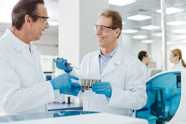 Bien hecho. compañeros encantados positivos de pie uno frente al otro y gesticulando activamente mientras hacen análisis de sangre