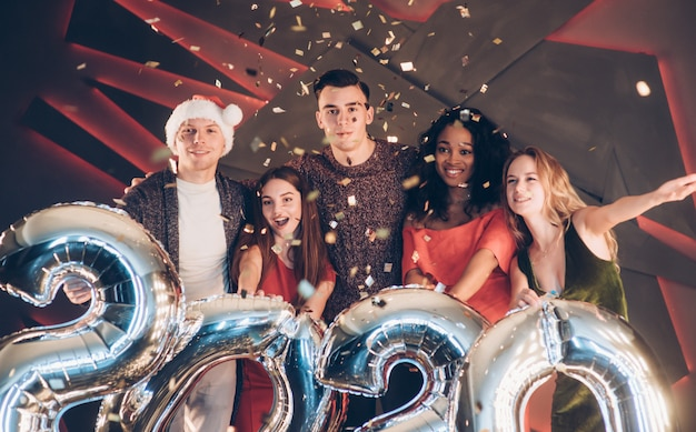 Está bien juntos. grupo de hermosas jóvenes amigos con números inflables en manos celebrando el nuevo año 2020