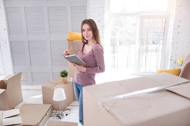 Bien organizado. encantadora joven escribiendo en su cuaderno y creando la lista de sus pertenencias, preparándose para mudarse del piso