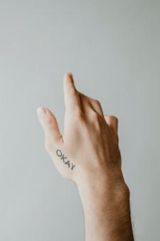 Bien, palabra tatuada en una mano