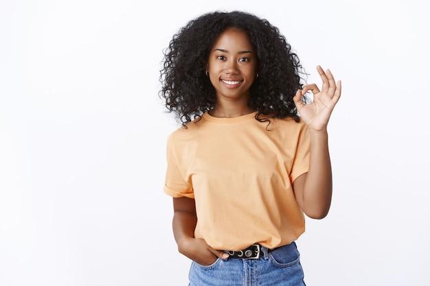 Bien vale. encantadora chica afroamericana con estilo de aspecto amigable dice que no hay problema en mostrar ok excelente gesto sonriendo satisfecho satisfecho buen resultado, dar recomendación de pared blanca de pie