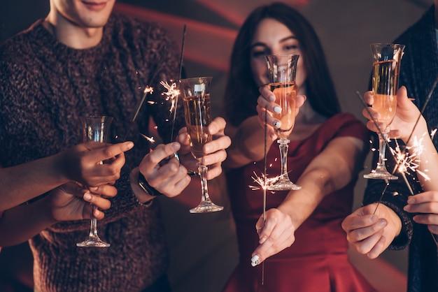 Bien vestido amigos multirraciales celebran año nuevo y sostienen luces de bengala y vasos con bebida