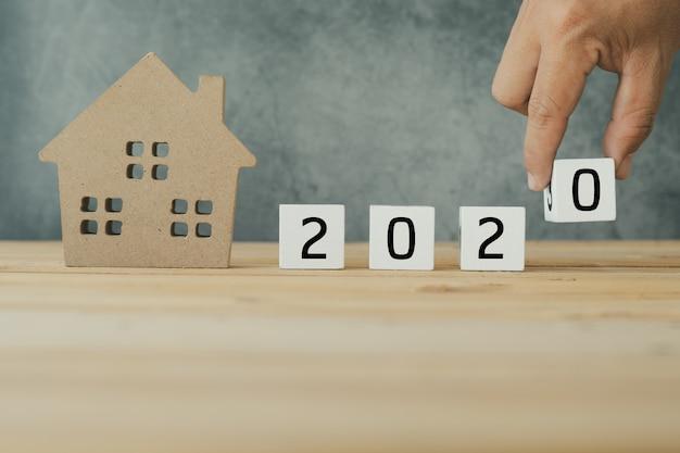 Bienes raíces en 2020, primer plano puesto a mano con pequeña casa de madera en la mesa