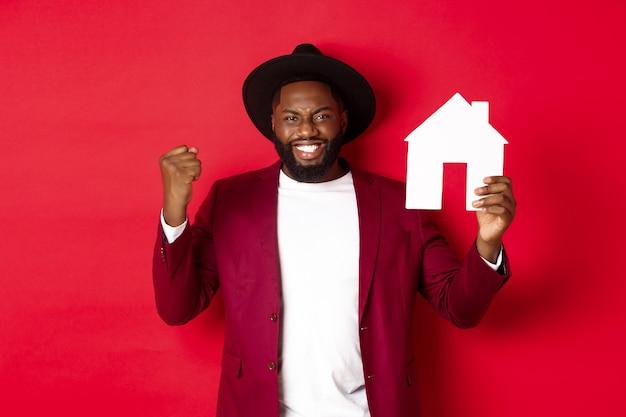 Bienes raíces. alegre hombre negro regocijándose y mostrando el mercado de casa de papel, de pie sobre fondo rojo.