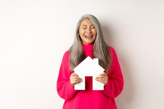 Bienes raíces. feliz abuela asiática riendo con los ojos cerrados, sosteniendo el modelo de la casa de papel, soñando con el modelo de la casa de papel, de pie sobre el fondo blanco.