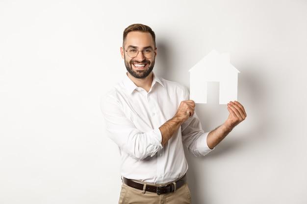 Bienes raíces. hombre guapo mostrando modelo de casa y sonriente, corredor mostrando apartamentos, de pie sobre fondo blanco.