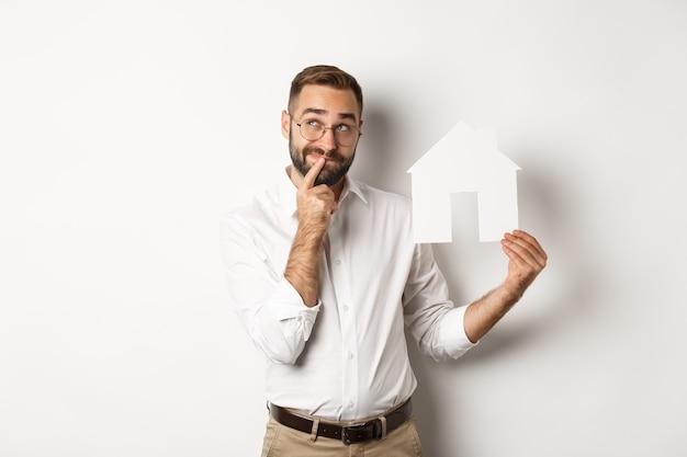 Bienes raíces. hombre pensando mientras busca apartamento, sosteniendo el modelo de casa de papel, de pie sobre fondo blanco.